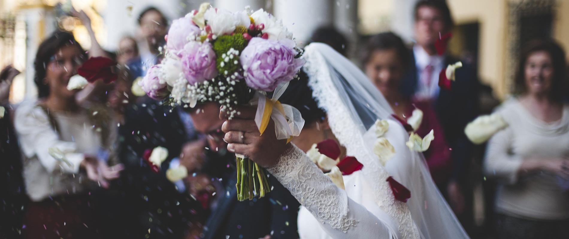 Eine Frau hält ihren Blumenstrauß an ihrer Hochzeit in die Höhe